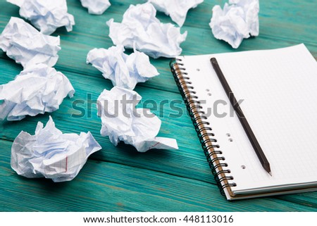 Creativity concept - notepad, pencil and crumpled paper on blue wooden table - stock photo