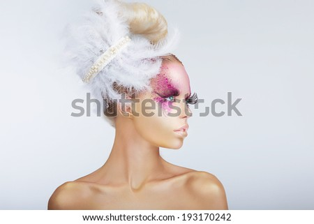 Creativity. Glamorous Fashion Model with Fancy Hair-do with Feathers - stock photo