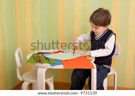 Creativity moment. Small boy creating piece of art with pencils, color paper and scissors. - stock photo