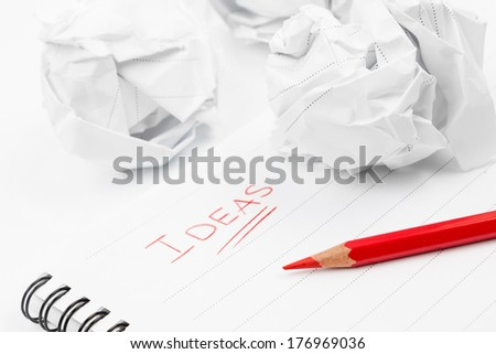 Creativity problems. Blank sheet of paper, red pencil, word Ideas and crumpled paper wads  - stock photo