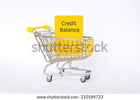 Credit balance in yellow shopping trolley on white, copy space - stock photo