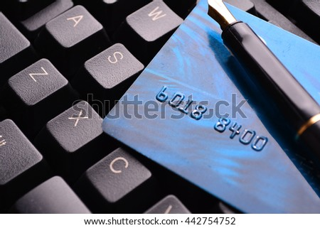 Credit card and fountain pen on a laptop. Selective focus, soft focus and shallow depth of fields - DOF