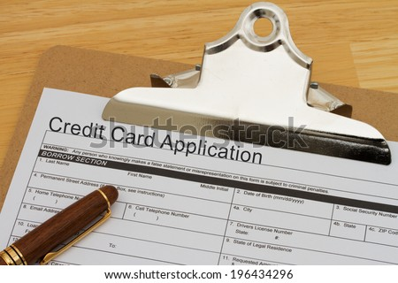 Credit Card Application Form on a clipboard with a pen on a wooden desk - stock photo
