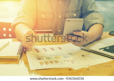 credit card,for shopping online,Woman verifies account balance on smartphone with mobile banking application.Online payment,hands holding a credit card and phone for online shopping,vintage color - stock photo