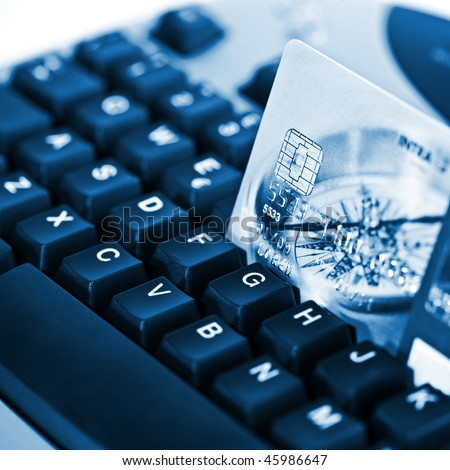 Credit card on a computer keyboard 04 blue - stock photo