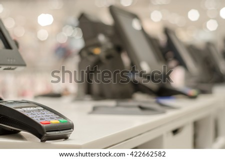 Credit card reader at the table with a cash register and computers - stock photo