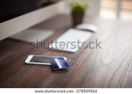 Credit card sitting on a smartphone next to a desktop computer on a modern workspace with shallow depth of field - stock photo