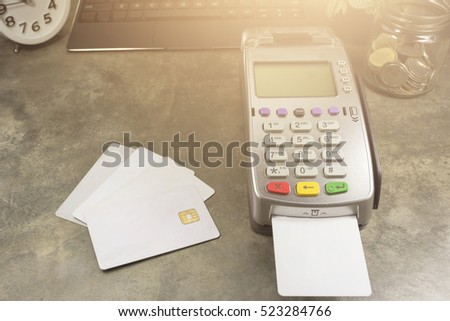 Credit Card Terminal or EDC on cashier table in the store with calculator, clock,coins in the bottle, credit cards and laptop on cashier table background with copy space.