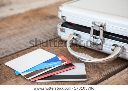 Credit cards and opened steel case laying on wooden floor - stock photo