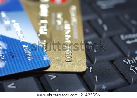 Credit cards laying on laptop's keyboard. - stock photo