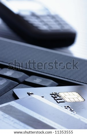 Credit cards on notebook and mobil phone. Focus on card, shallow DOF. - stock photo