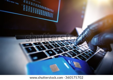 Credit Cards Theft Concept. Hacker with Credit Cards on His Laptop Using Them For Unauthorized Shopping. Unauthorized Payments - stock photo