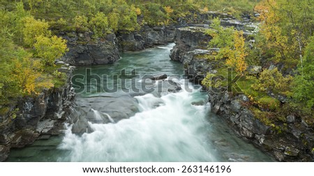 Creek, brook, river up North. Rocky canyon and vegetation around the water. - stock photo