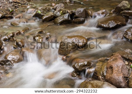 Creek flowing over the rocks. Long exposure giving smooth water surface - stock photo