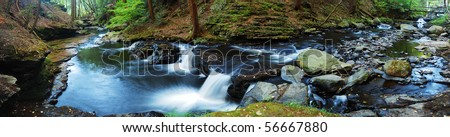 Creek panorama with wood bridge and hiking trail in woods in autumn with rocks and foliage. - stock photo