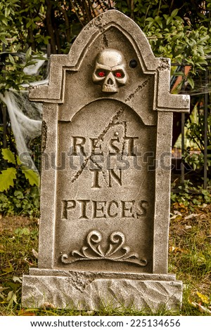 Creepy Halloween skeleton gravestone  with rest in pieces message on front - stock photo