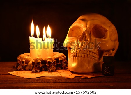 Creepy human skull with evil candles burning on wooden background in the darkness - stock photo