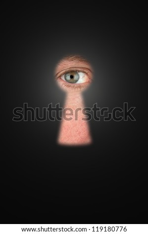 Creepy man peeking through a keyhole with focus on his eyeball. - stock photo