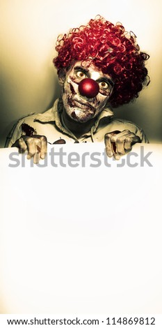 Creepy Monster Clown Holding Blank White Sign When Advertising Horrific Halloween Discounts - stock photo