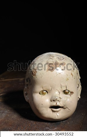 Creepy old doll head sitting on weathered wood