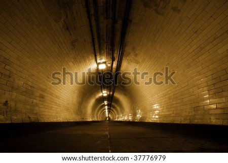 Creepy old tunnel below Thames river - stock photo