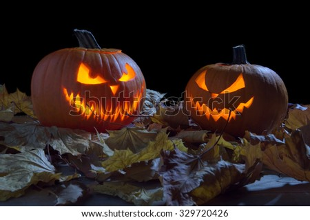 Creepy two pumpkins as jack o lantern among dried leaves on black background - stock photo