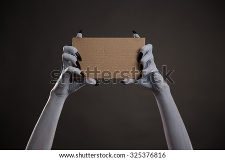 Creepy white hands with black nails holding blank cardboard, Halloween theme  - stock photo
