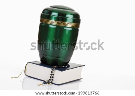 Cremation urn with bible and rosary - stock photo