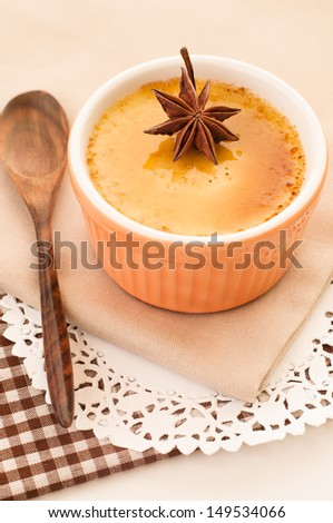 Creme brulee dessert garnished with a star aniseed. - stock photo