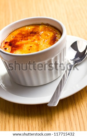 creme brulee in ceramic bowl on kitchen table - stock photo