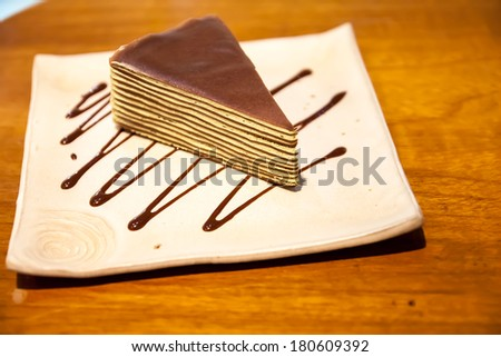Crepe cake in square japanese-style dish on the wood table with zigzag chocolate sauce. - stock photo