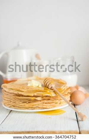 Crepes or pancakes with butter and honey, selective focus - stock photo