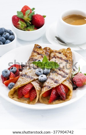 crepes with berries and chocolate sauce for breakfast, vertical, closeup - stock photo