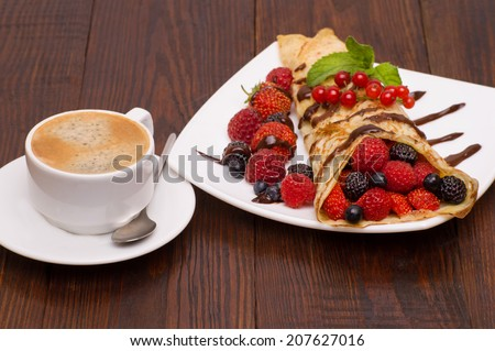 Crepes With Berries and cup of coffee . Crepe with Strawberry, Raspberry, Blueberry and Chocolate topping. Pancake - stock photo