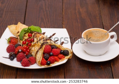 Crepes With Berries and cup of coffee . Crepe with Strawberry, Raspberry, Blueberry and Chocolate topping. Pancake