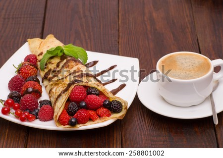 Crepes With Berries and cup of coffee. Crepe with Strawberry, Raspberry, Blueberry and Chocolate topping. Pancake - stock photo