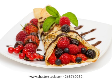 Crepes With Berries isolated on white background . Crepe with Strawberry, Raspberry, Blueberry and Chocolate topping. Pancake - stock photo