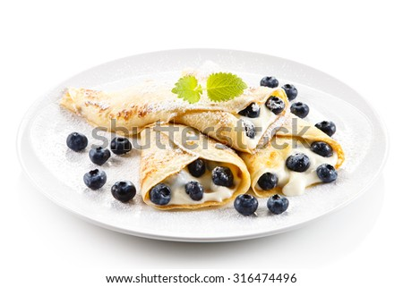 Crepes with blueberries and cream on white background  - stock photo
