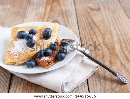 Crepes with blueberries and sugar powder - stock photo