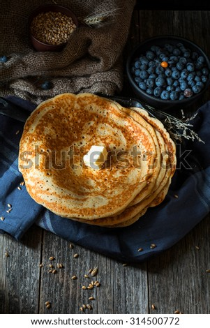 Crepes with butter and blueberries on rustic wooden background, high angle view, natural morning light - stock photo