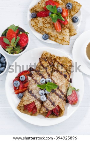 crepes with fresh berries and chocolate sauce for breakfast, top view, vertical, closeup - stock photo