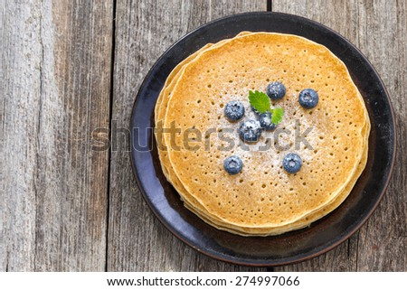 crepes with fresh blueberries on wooden table, top view, horizontal - stock photo