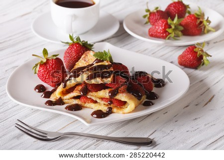 crepes with strawberries and coffee on a table close-up. Horizontal
