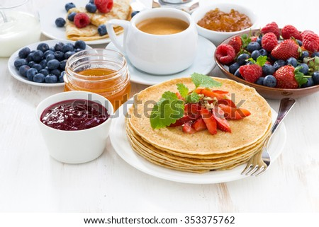 crepes with strawberry, jams and honey on white wooden background, horizontal, close-up - stock photo