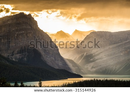 Crepuscular rays shine through clouds over Hector Lake in Banff National Park, Canada. - stock photo
