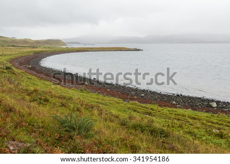 Crescent shaped rocky beach on a misty day near Dunvegan castle in Skye, in the Inner Hebrides of Scotland. Pebbles, stones and coral sand are usual beach elements at the entrance to Loch Dunvegan. - stock photo