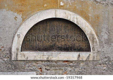 crescent-shaped window with safety net and the wall crumbling - stock photo