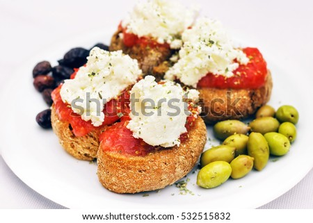 Cretan appetizer - dakos, rusk with tomato sauce, olives and local staka cheese (selective focus)