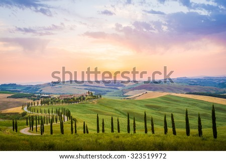 Crete Senesi, Tuscany, Italy. A lonely farmhouse with cypress and olive trees, rolling hills, Tuscany, Italy. A lonely farmhouse with cypress and olive trees, rolling hills. - stock photo