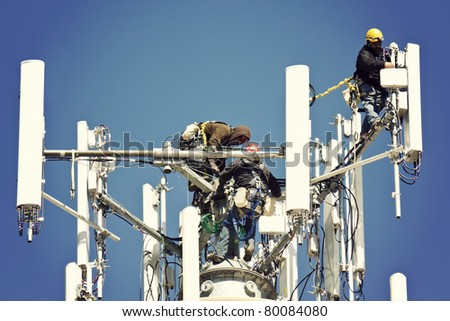 Crew installing antennas on the top of 150' water tower - stock photo